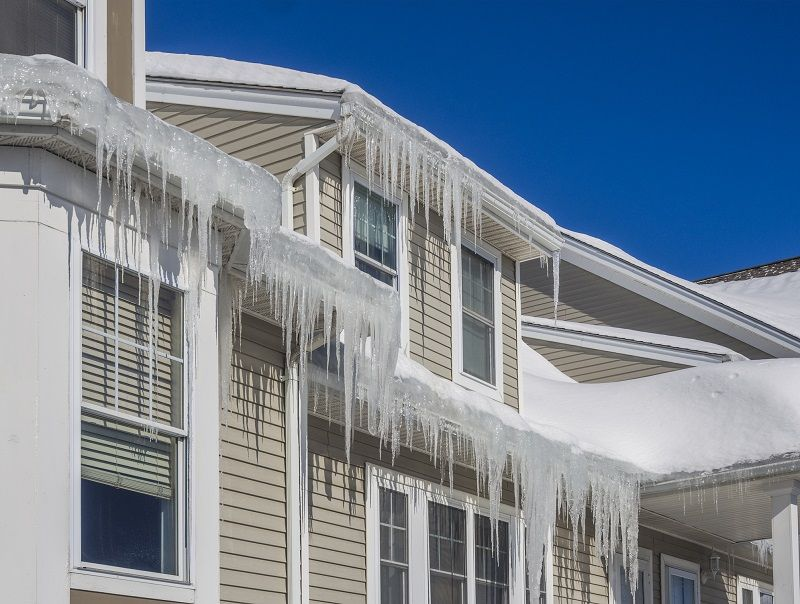 Icicles, ice dams and snow on roof and gutters
